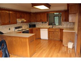 a large kitchen with appliances and wooden cabinet